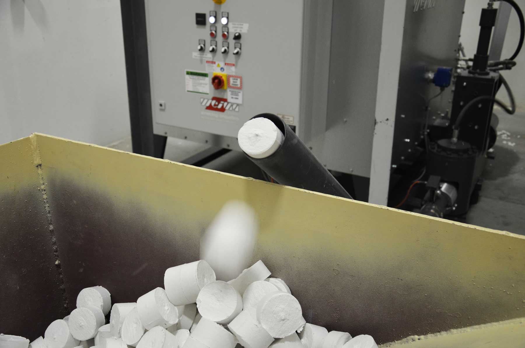 Papierbrikett fällt aus der Brikettierpresse in Behälter