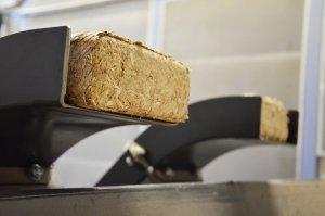 Holzbriketts beim Austrag aus einer TH 1500 Presse
