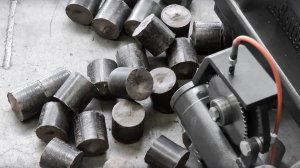 Austrag von Holz-Staub-Briketts einer TH 714 Brikettierpresse