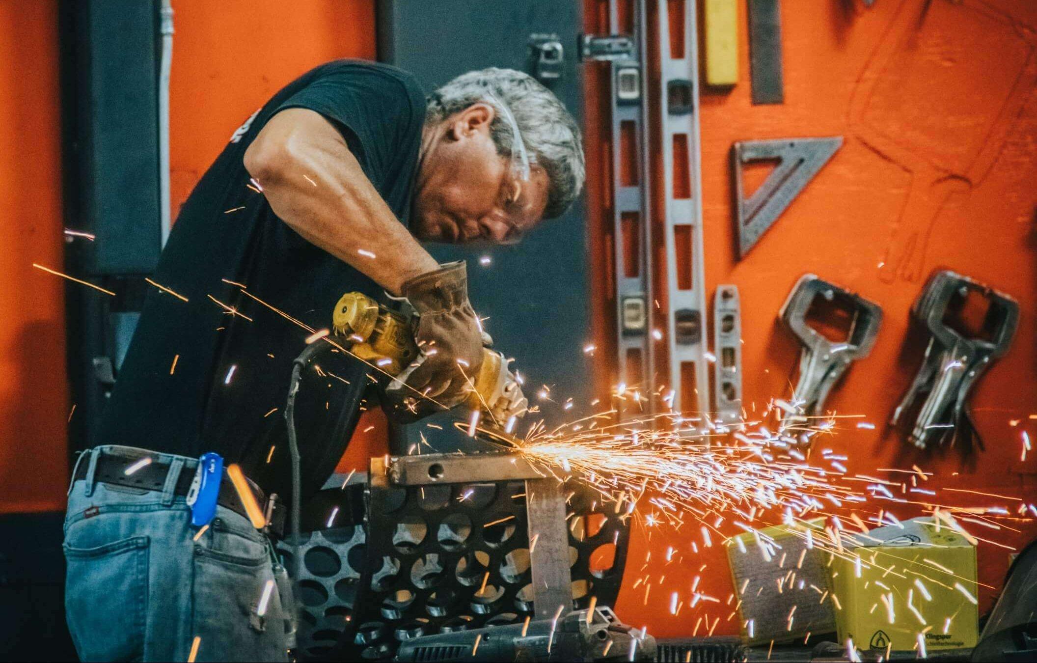 WEIMA fabricator, Burt Sanders, grinding a metal screen