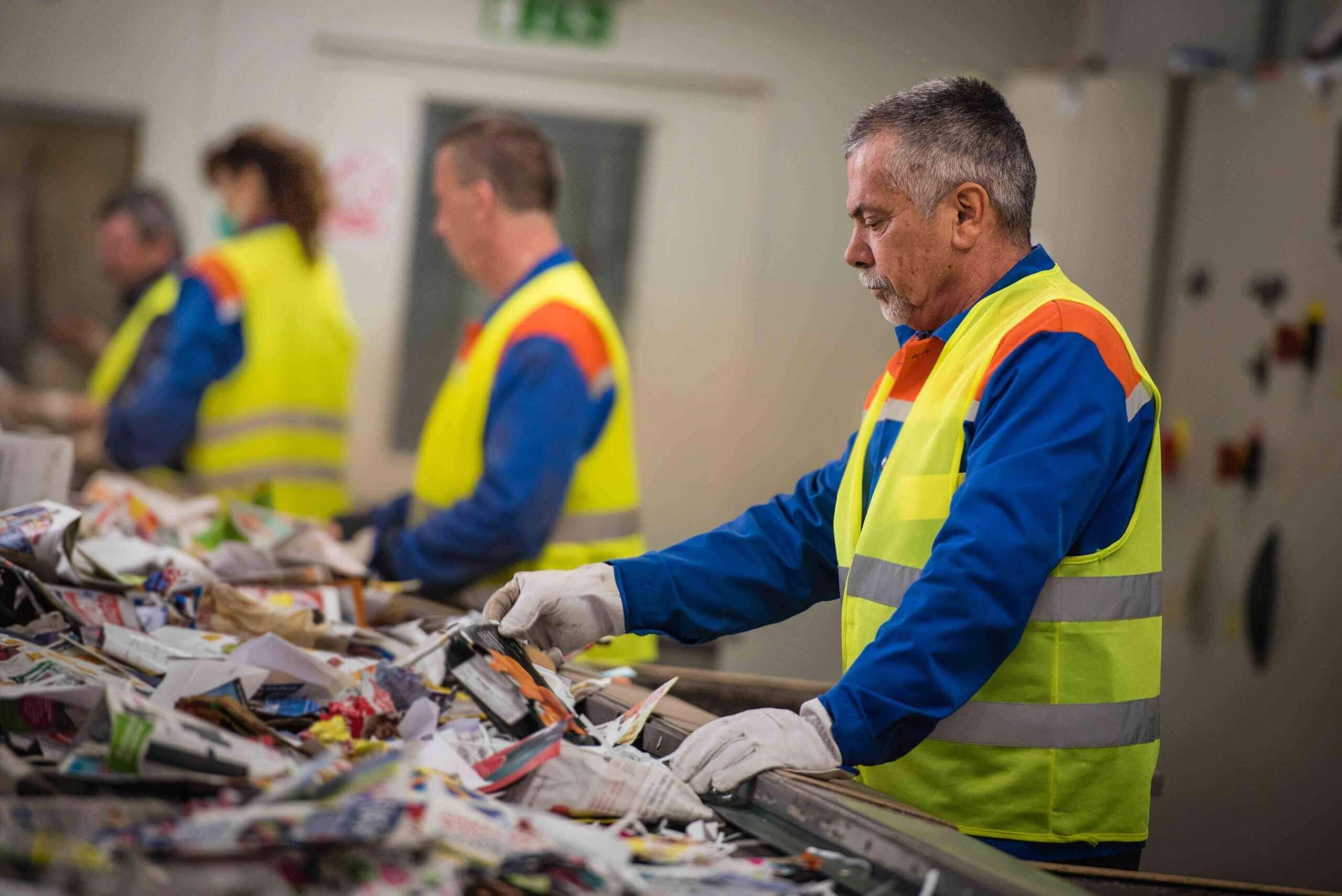 Arbeiter sortieren Müll in einer Recyclinganlage