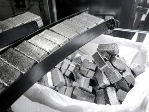 Hochverdichtete Aluminium Briketts werden aus der Brikettierpresse ausgestoßen