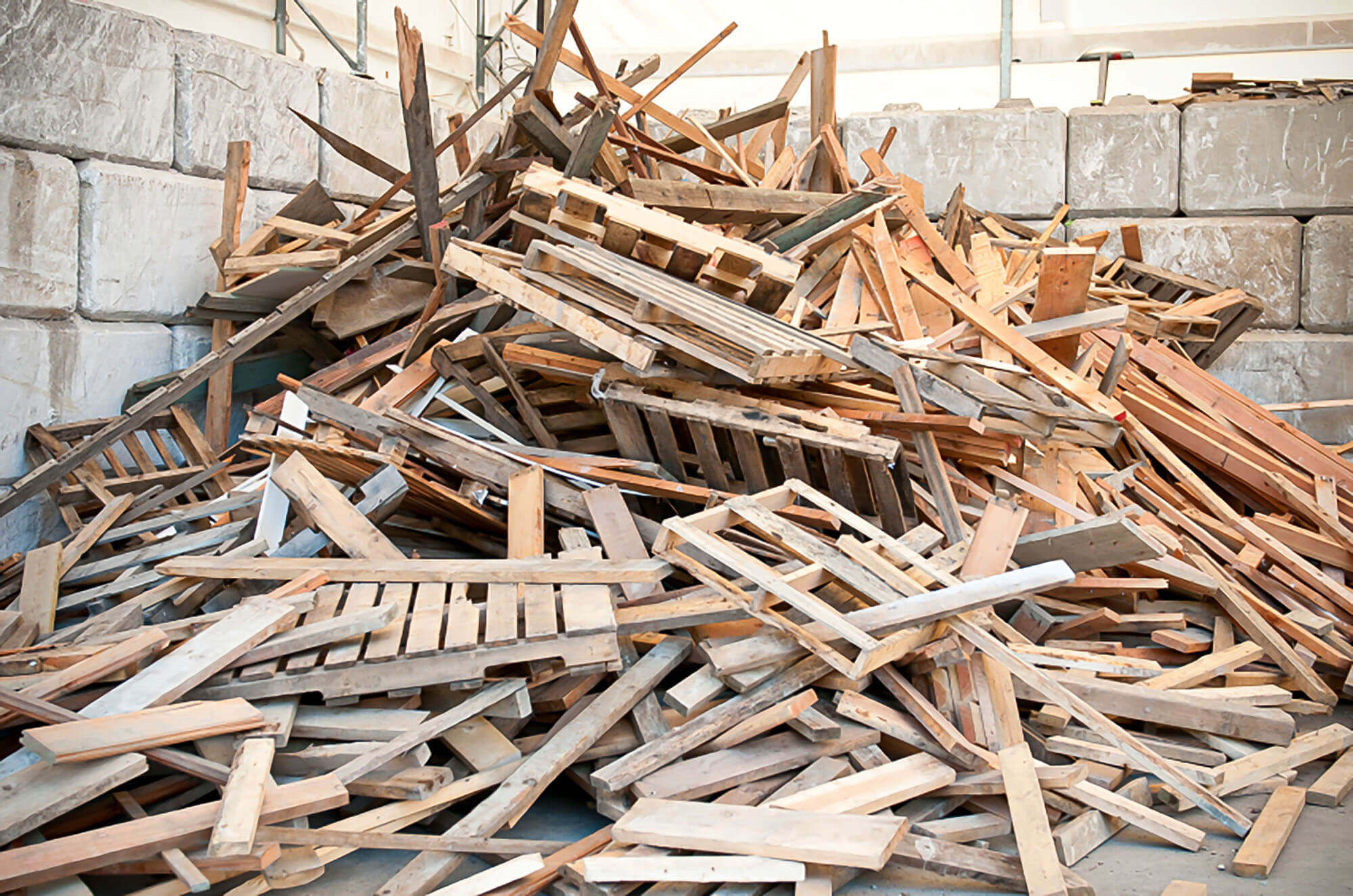 A pile of waste wood with wooden pallets and wooden furniture