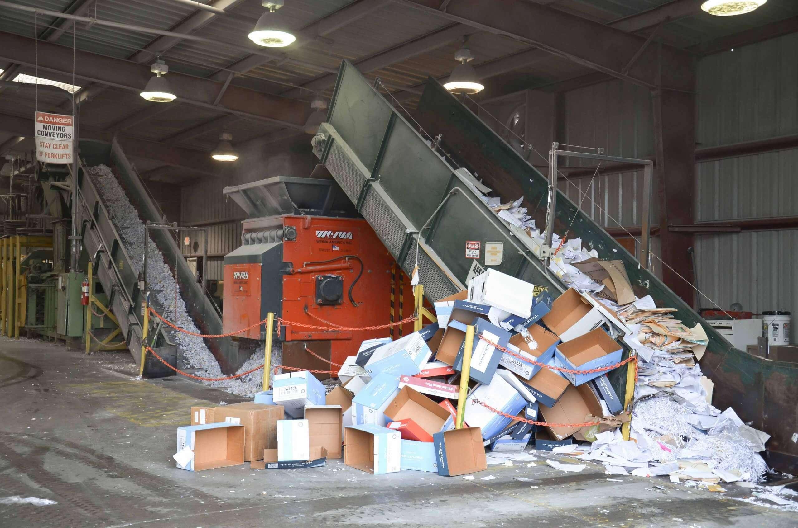 Kartons und Kartonage werden per Förderband dem WEIMA Zerkleinerer zugeführt