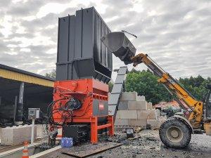 Radlader befüllt WEIMA PowerLine Shredder mit Müllcontainern und Plastikrohren