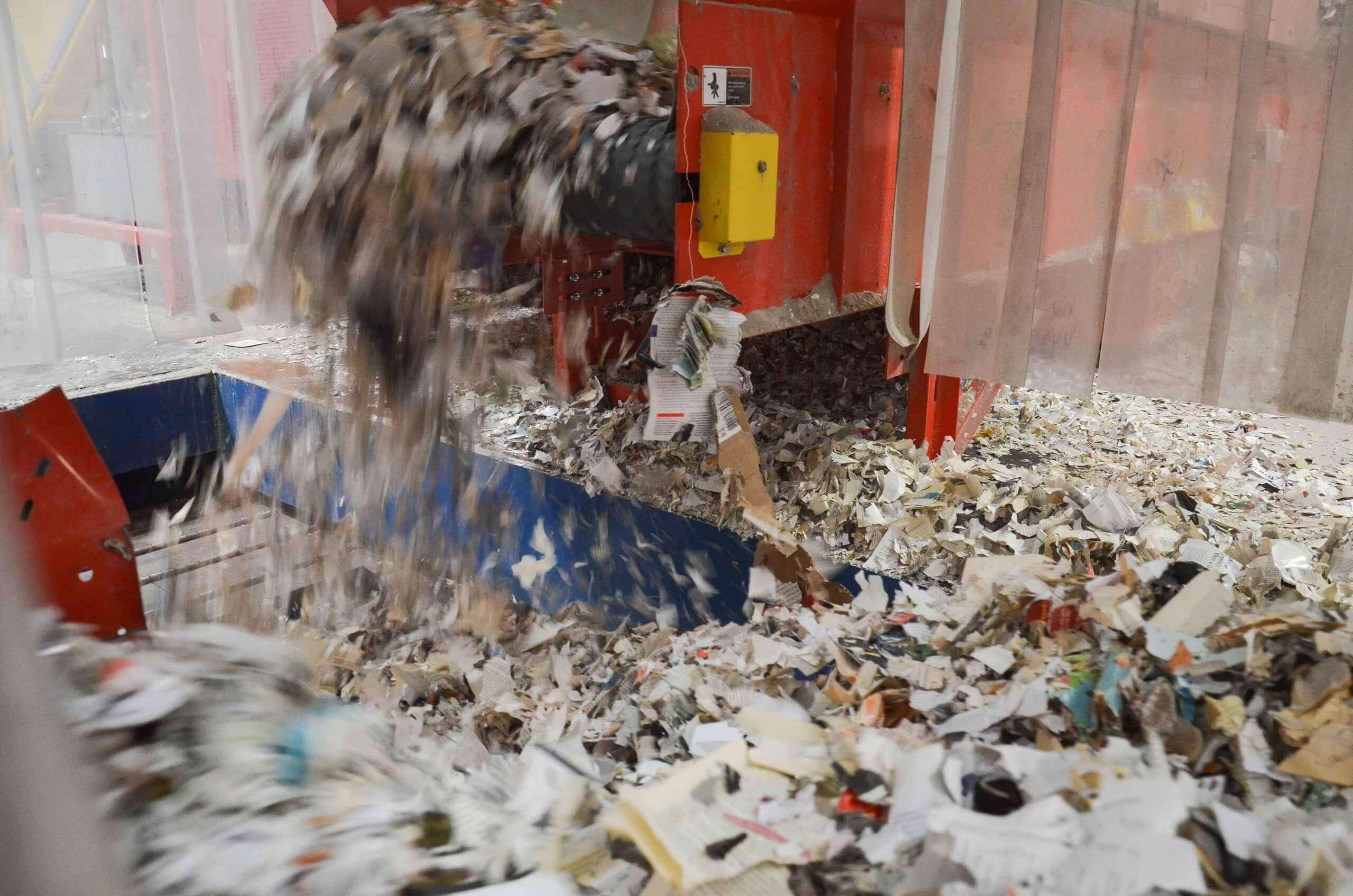 Geshredderte Zeitungen fallen aus der Maschine auf das Förderband.