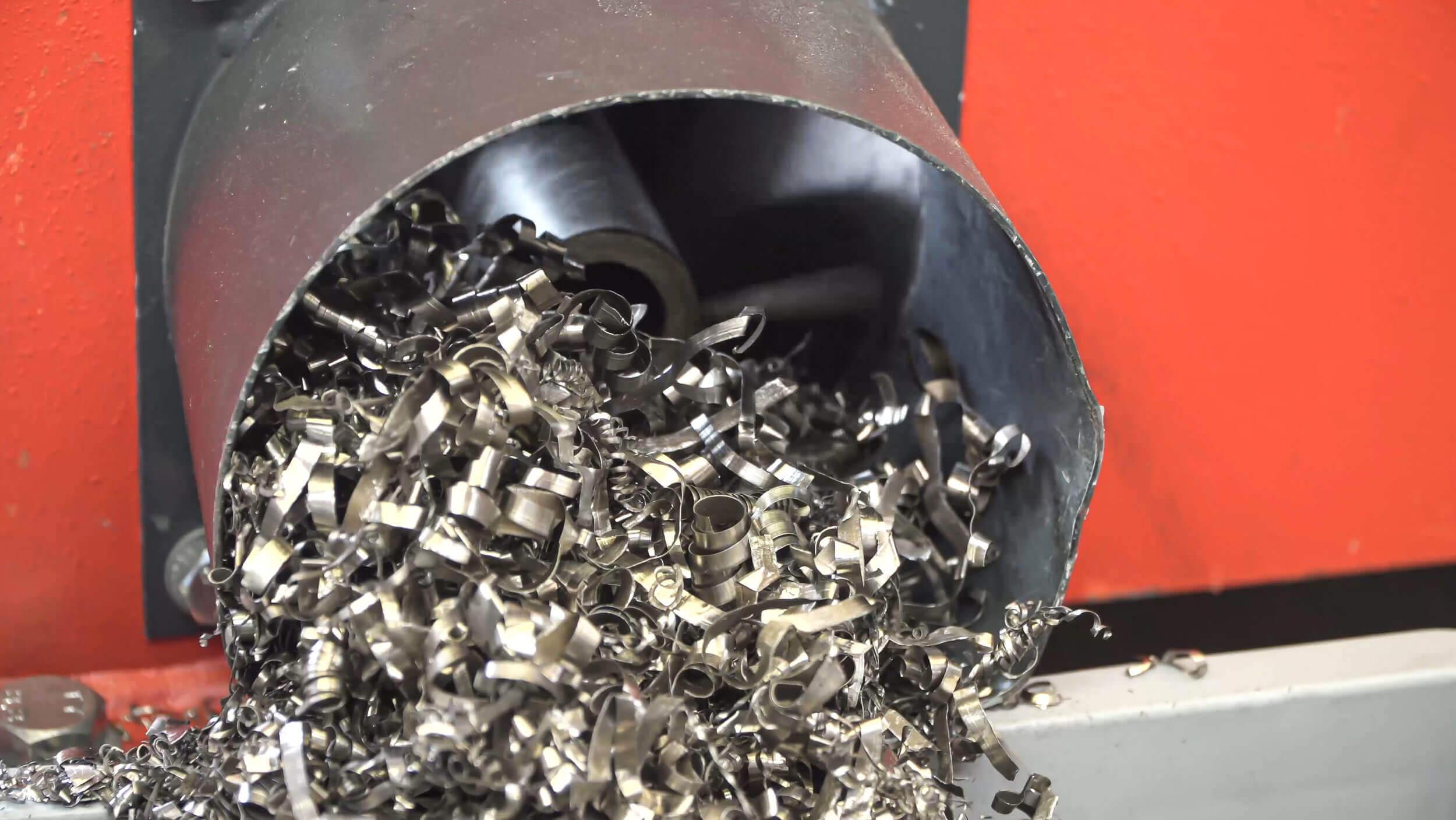 Shredded metal shavings in the screw conveyor discharge