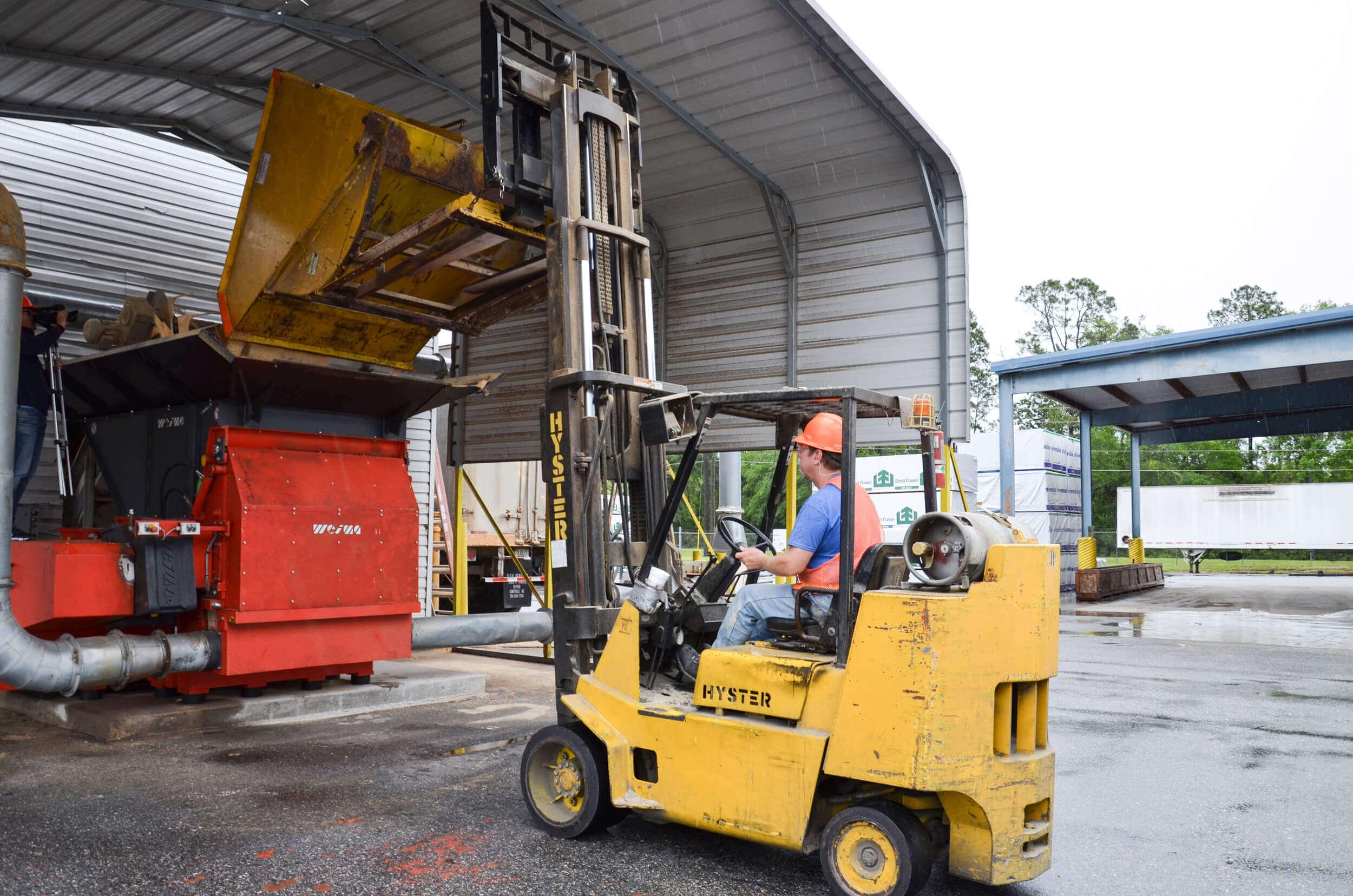 Forklift truck tips wood waste into WEIMA WLK 15 shredder
