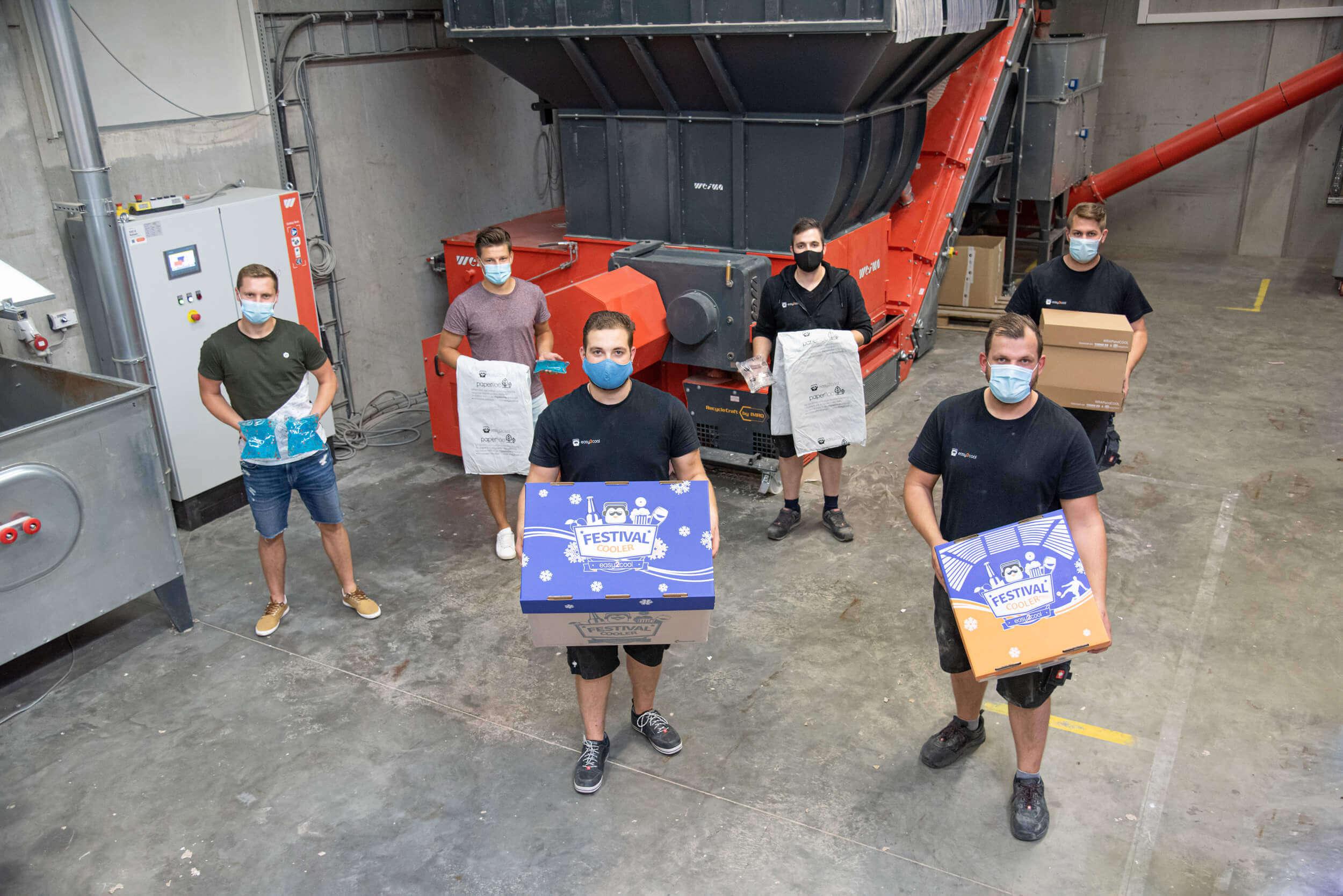 Mitarbeiter der easy2cool GmbH vor dem WEIMA Zerkleinerer mit den Produkten