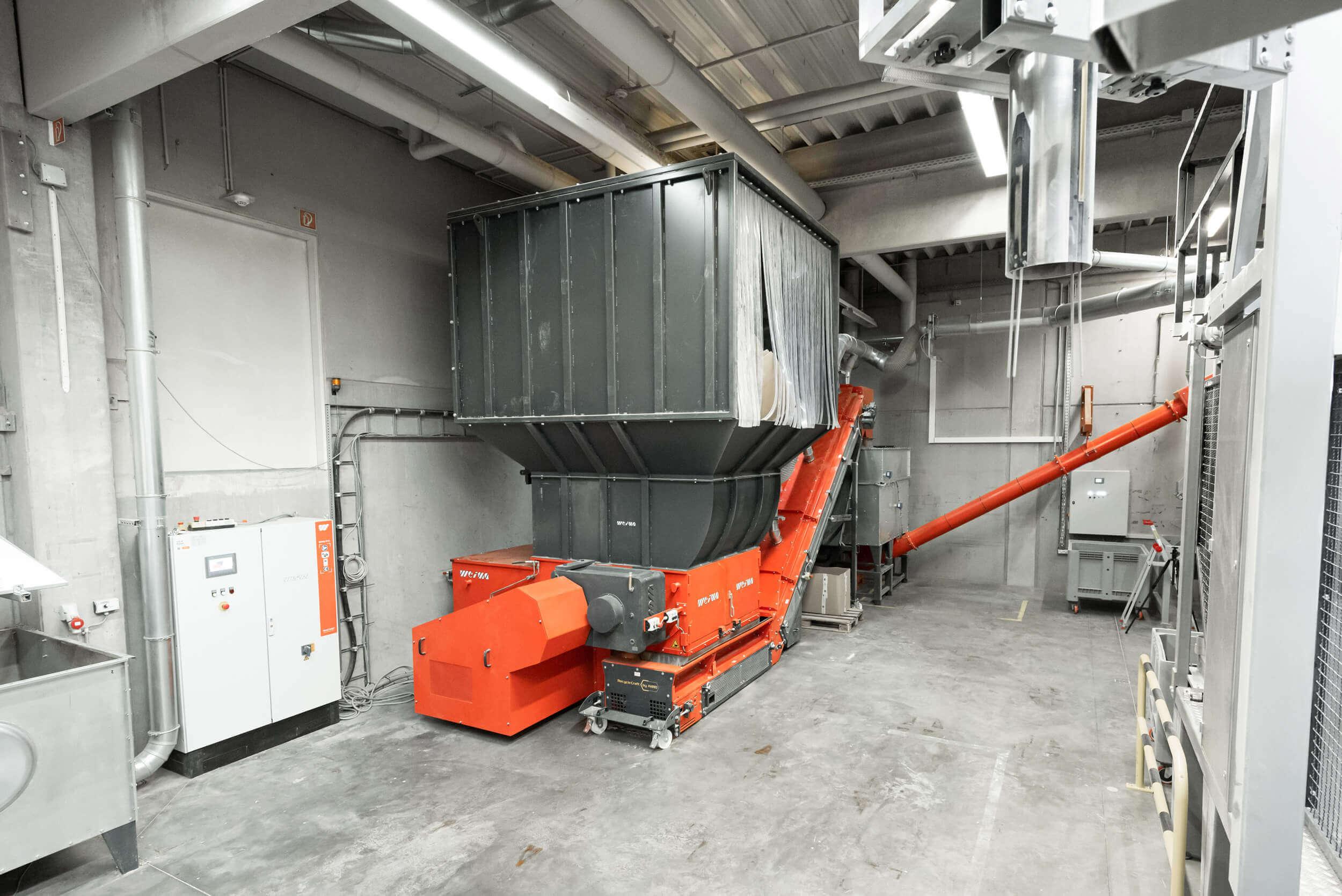 WEIMA lieferte eine Systemlösung mit Shredder, geschlossenem Förderband, Absaugstutzen, Dosieranlage