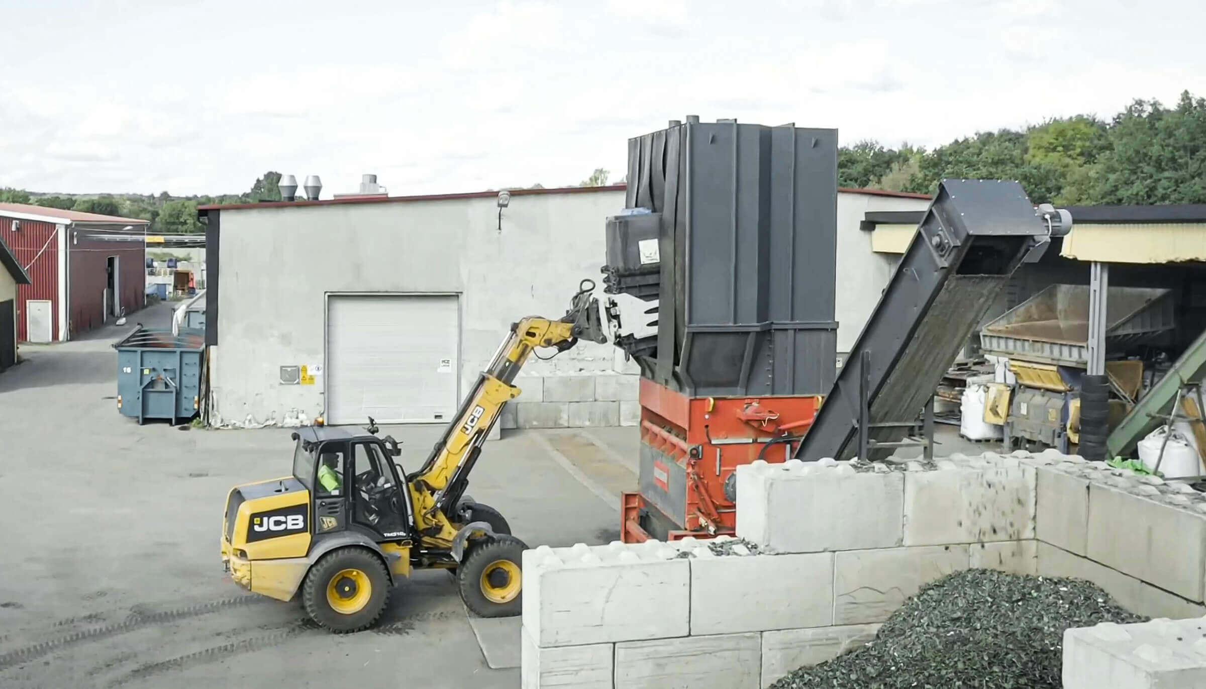 WEIMA Einwellen-Zerkleinerer PowerLine wird mit einem Radlader mit Mülltonnen zum Shreddern befüllt