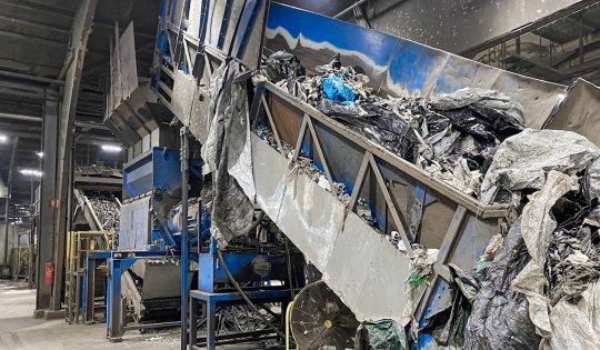 Verunreinigte Landwirtschaftsfolie wird mithilfe eines Förderbands in den Shredder transportiert