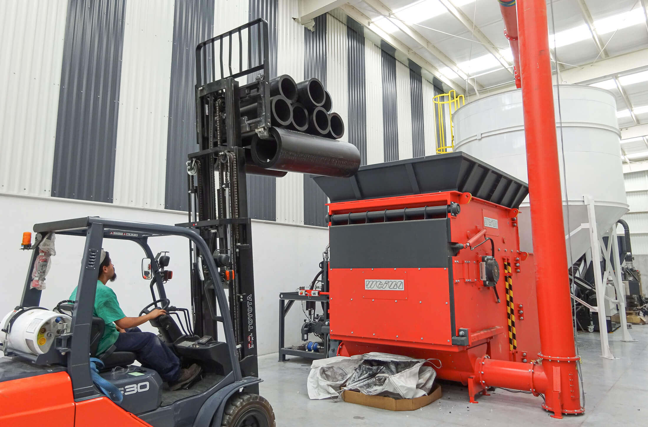 Wheel loader puts HDPE pipe cuttings into the hopper of the WEIMA shredder for recycling