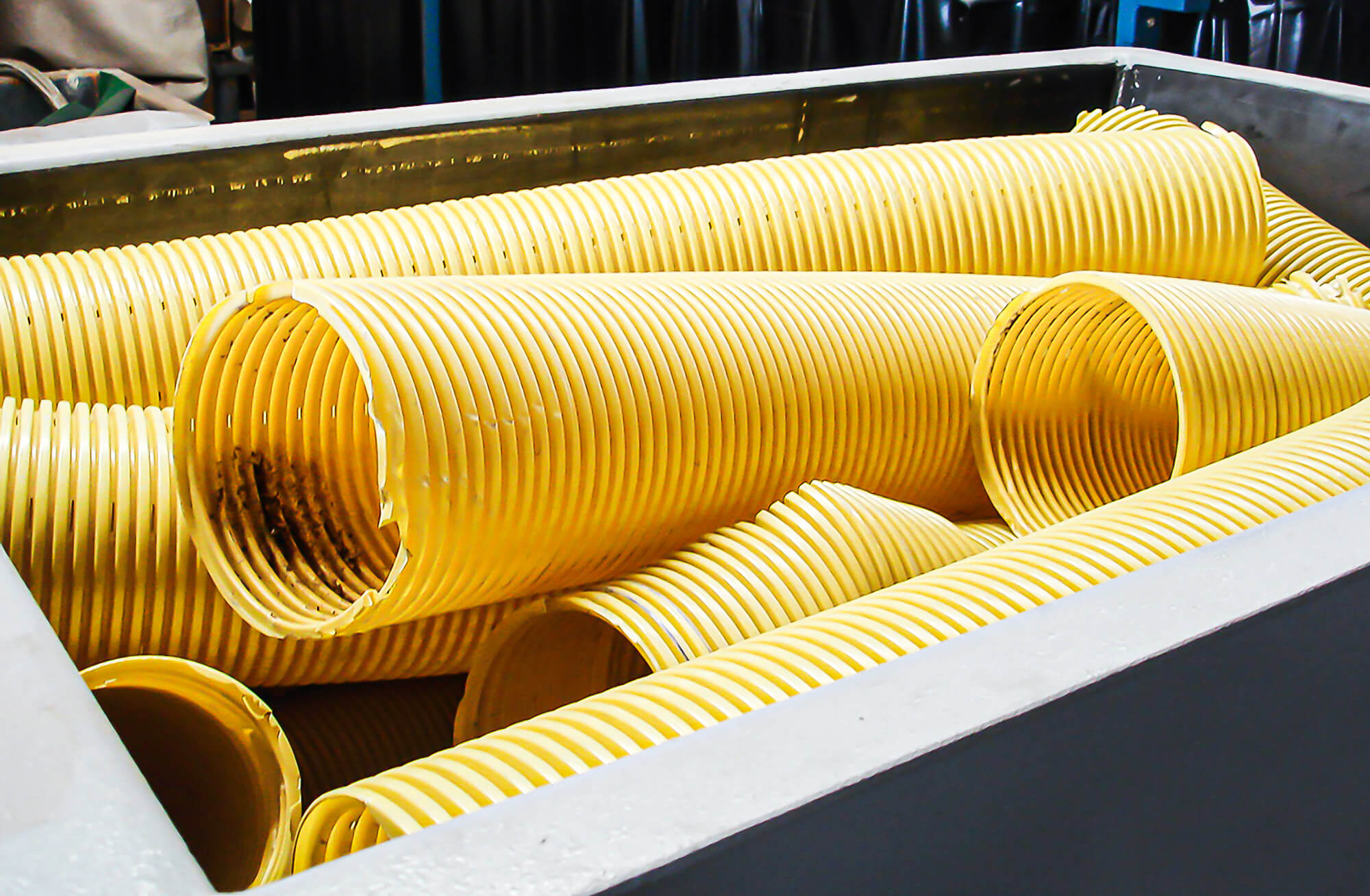 Polyvinyl chloride pipes are loaded into the WEIMA shredder